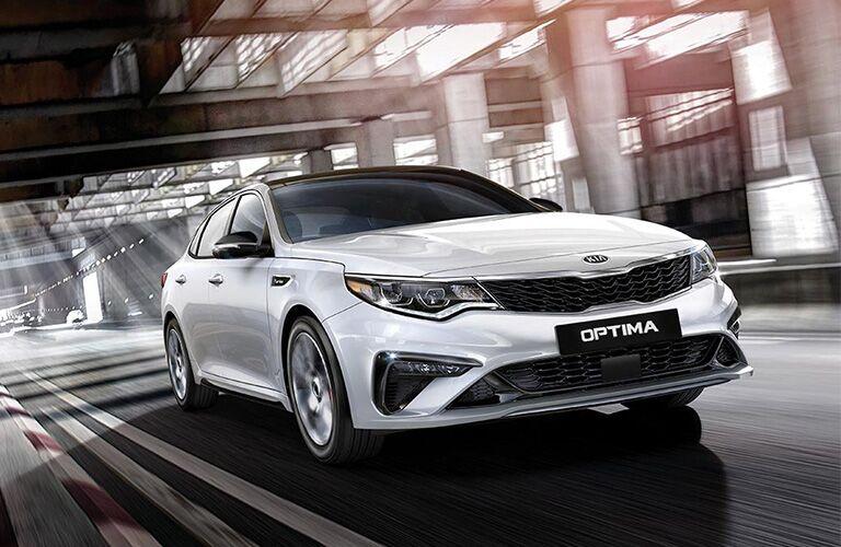2019 Kia Optima driving down a road.