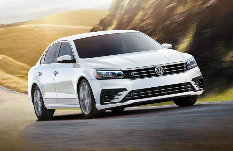 White 2016 Volkswagen Passat cruises up a country road.