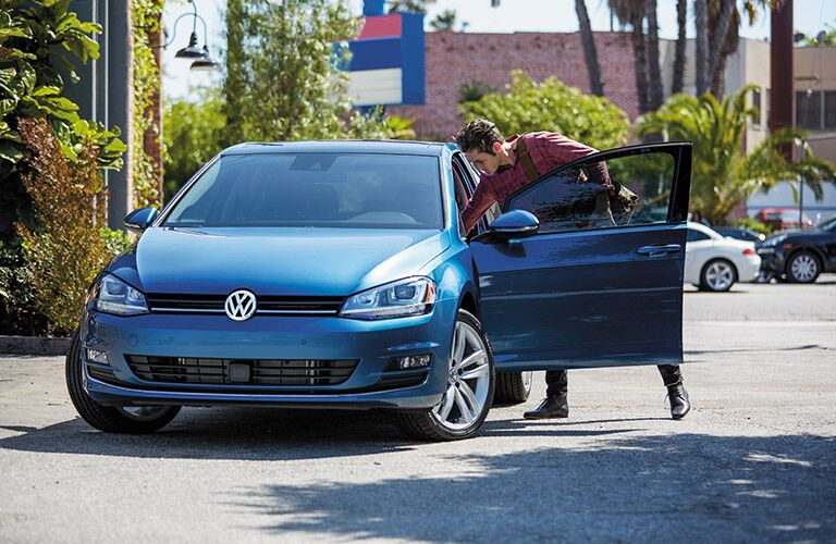 Man reaches in through the open driver's door of a blue 2016 Volkswagen Golf.