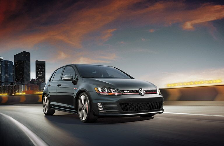 Dark forest green 2016 Volkswagen Golf GTI cruises up a highway with a city skyline far behind.