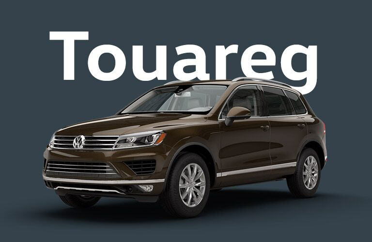 "Brown Volkswagen Touareg sits in front of a light black background under giant white text that reads, ""Touareg."""