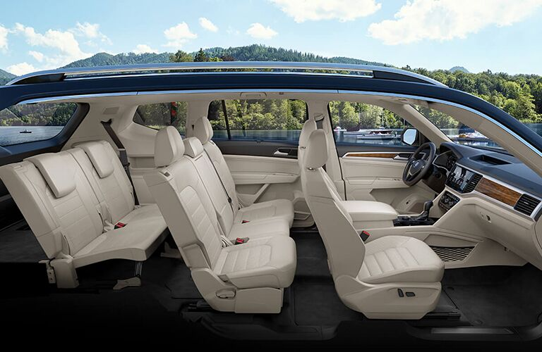 Cutaway side view of a 2019 Volkswagen Atlas, showcasing the three spacious rows of seating with a lake and forest backdrop.