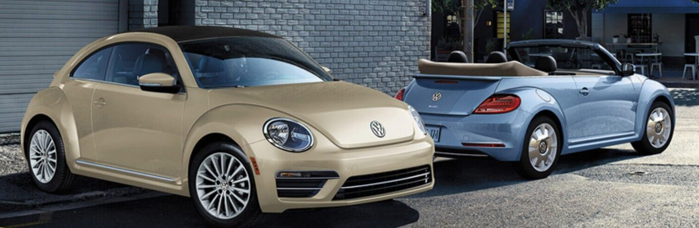 Two 2019 Volkswagen Beetle Convertible Final Edition models parked, one with the top up and one with it lowered.