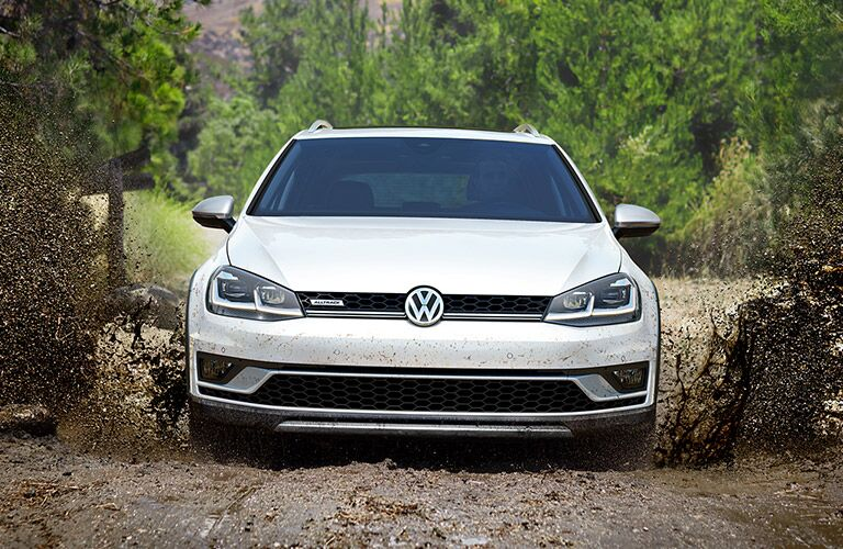 Head-on view of a white 2019 Volkswagen Golf Alltrack parked amidst some brush in a wooded area.