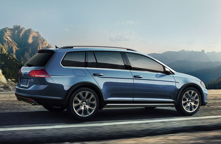 Side/rear view of a blue 2019 Volkswagen Golf Alltrack driving down a highway near a rugged wilderness.