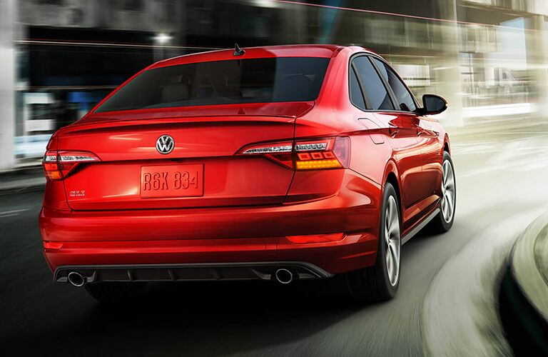 Red 2019 Volkswagen Jetta GLI rounds a curve. Exterior angled view of rear.
