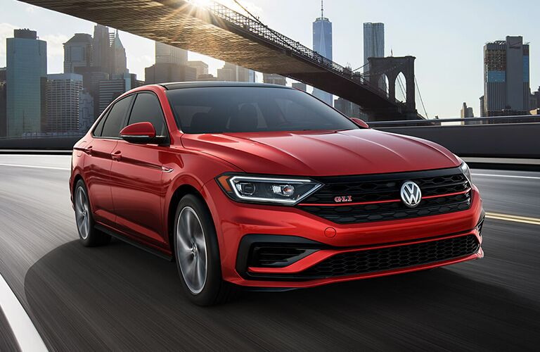 Red 2019 Volkswagen Jetta GLI drives alone down a city highway with a skyline backdrop and a bridge crossing above. Exterior angled front view.
