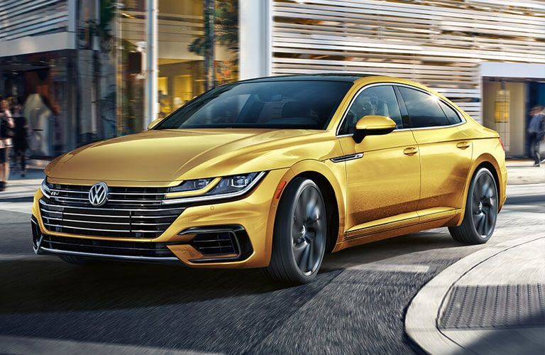 Yellow 2019 Volkswagen Arteon cruises around a corner in a city.