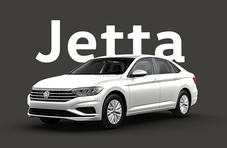 "Silver Volkswagen Jetta in front of a black background and gigantic white text that reads, ""Jetta."""