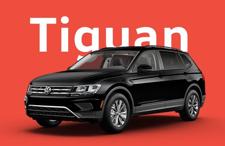 "Black Volkswagen Tiguan sits in front of a red background beneath giant white text that reads, ""Tiguan."""