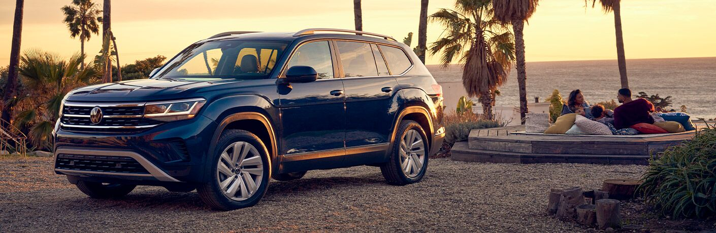2021 VW Atlas blue exterior front driver side parked near beach people sitting on benches