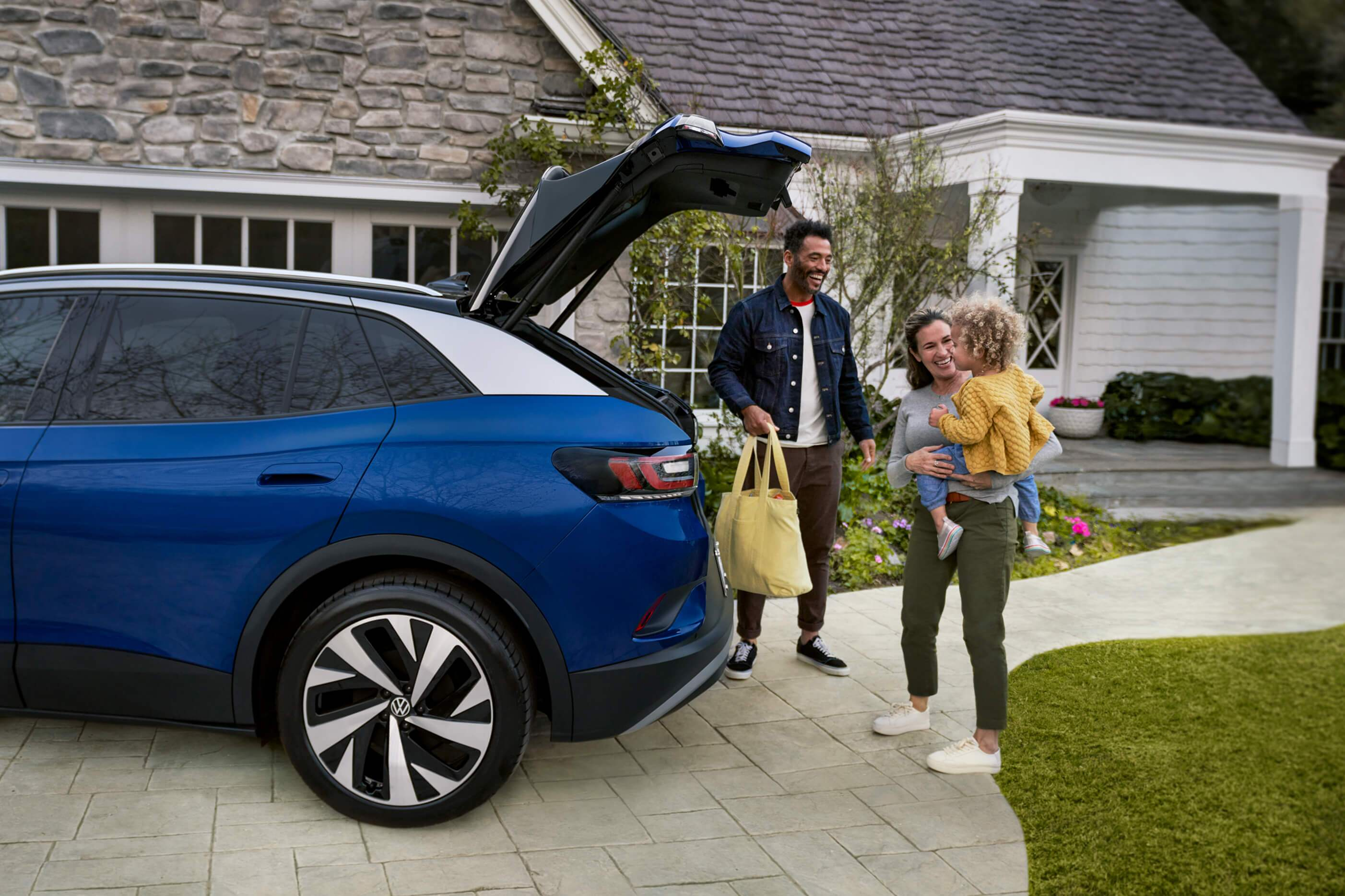 A young family loads a bag into the cargo area of an ID.4, shown in Dusk Blue Metallic parked in a residential driveway.