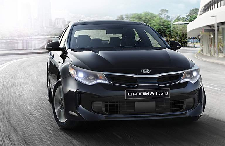 front view of a 2018 Kia Optima Hybrid driving in the city