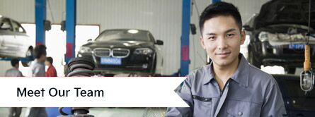 """Man in car shop looking at camera with car in background and """"Meet our Team"""" text"""