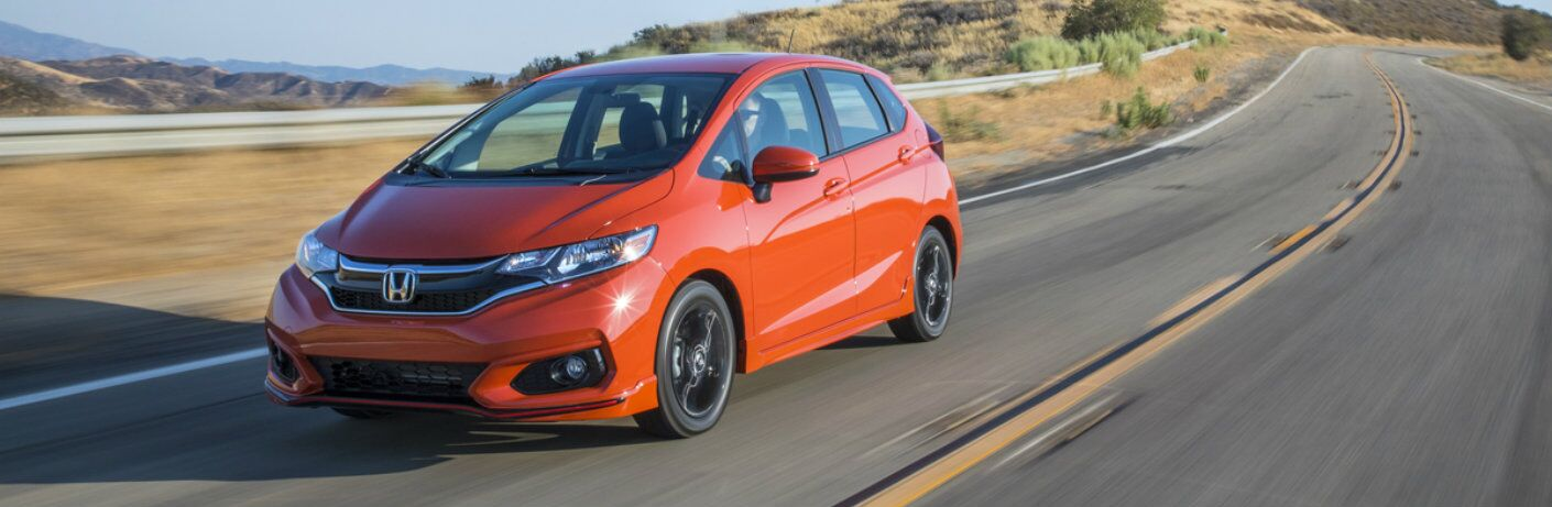 Front driver side exterior view of an orange 2019 Honda Fit