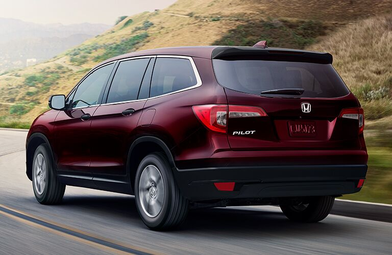 Rear driver side exterior view of a red 2019 Honda Pilot
