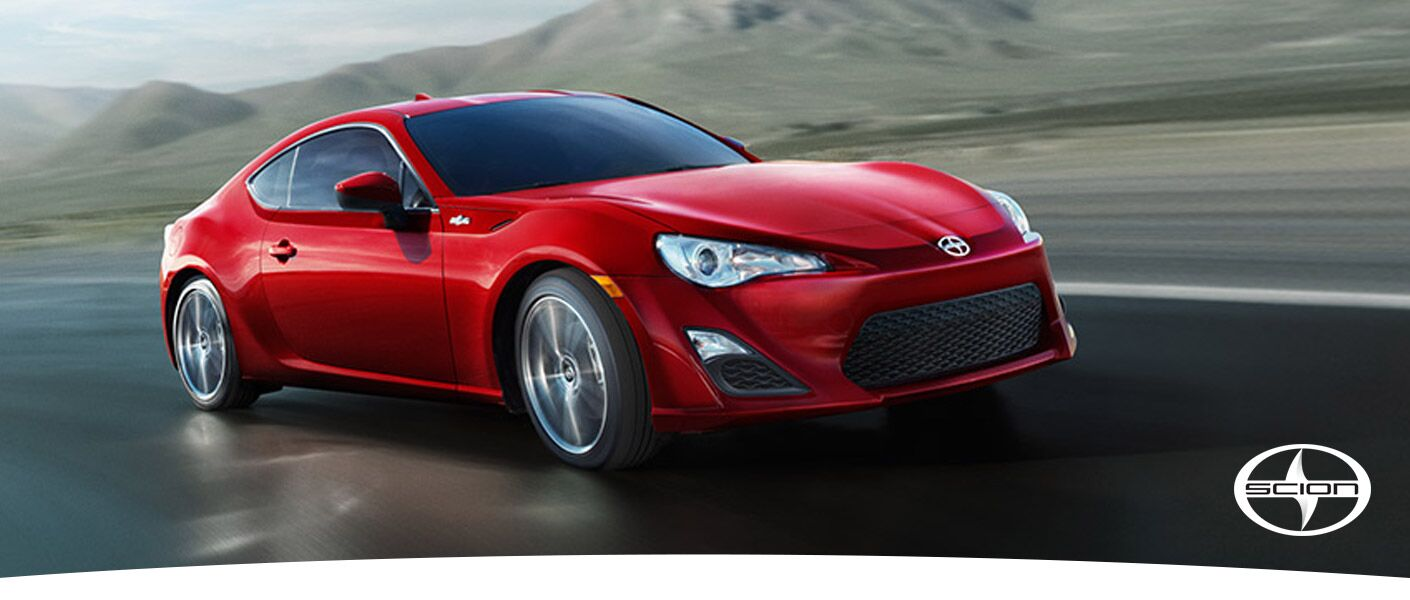 View of red 2016 Scion FR-S driving down road with mountains in the background and Scion Logo in lower right corner