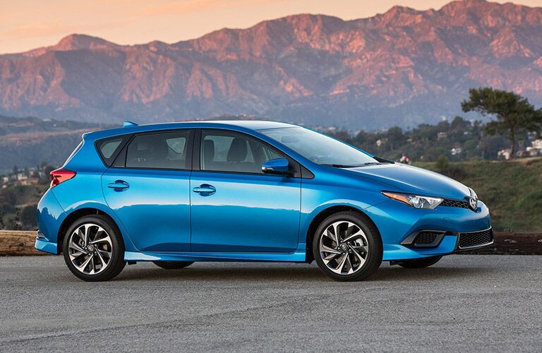 View of blue 2016 Scion iM parked on pavement with mountains in background