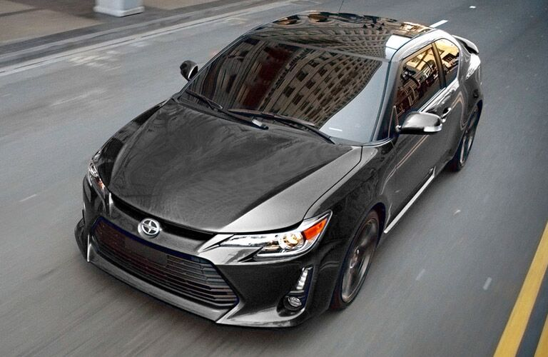 View of 2016 black Scion tC driving down a city street