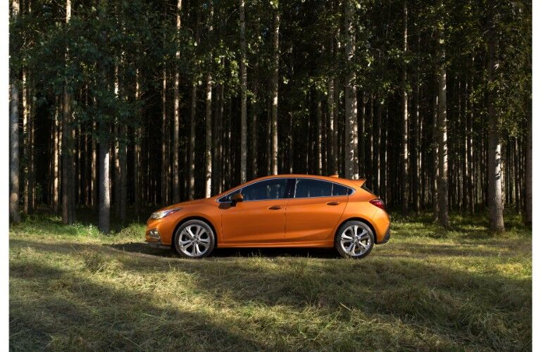 2018 Chevrolet Cruze hatchback exterior side shot orange paint parked in a wood forest clearing