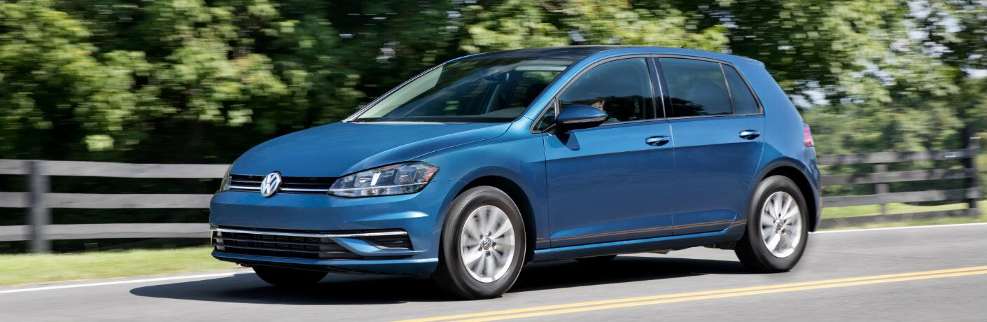 2018 Volkswagen Golf exterior shot silk blue metallic paint driving in the country next to a fence and bushed forest