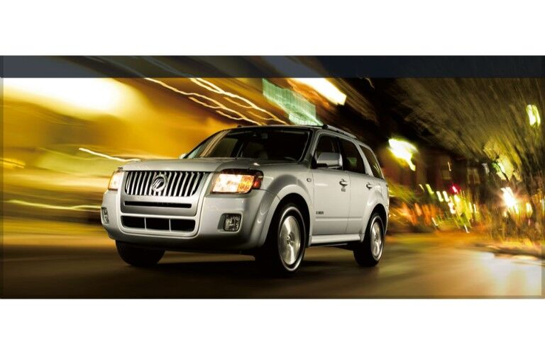 Mercury Mariner exterior shot driving through a city street with a yellow blurry background