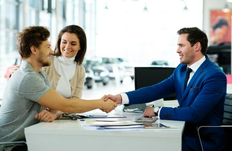 Salesman shaking hand after couple finishes contract