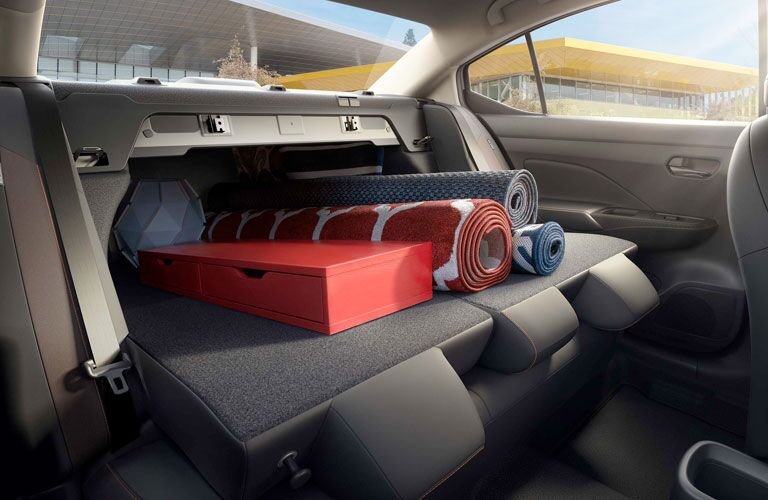 2020 Nissan Versa back seats folded down with rugs sticking out from the trunk