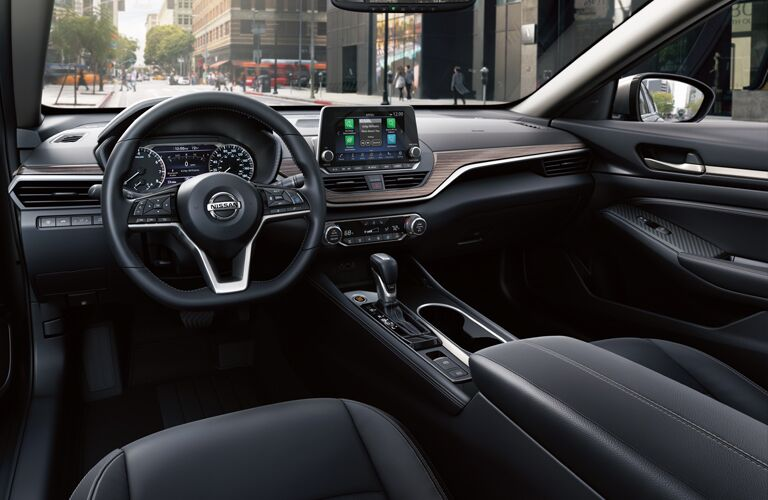 Interior cabin view of a 2019 Nissan Altima, showcasing the steering wheel, dash, infotainment, and view through the windshield/windows.