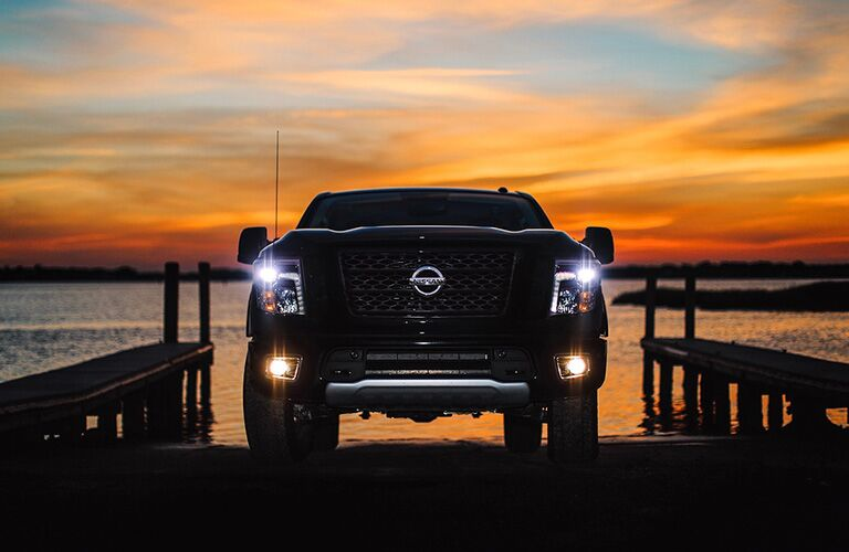 front view of black 2019 nissan titan xd with headlights on at boat launch