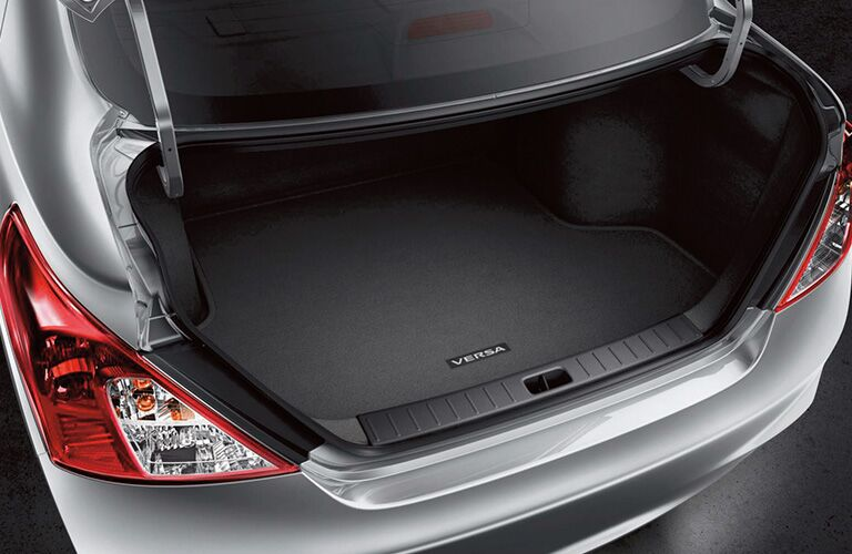 Open rear trunk of a silver 2019 Nissan Versa sedan.