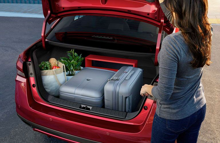 Woman looking at the open trunk that has bags in the 2020 Nissan Versa