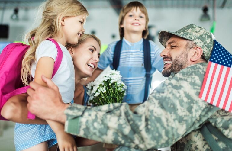 A member of the military is welcomed home by his family