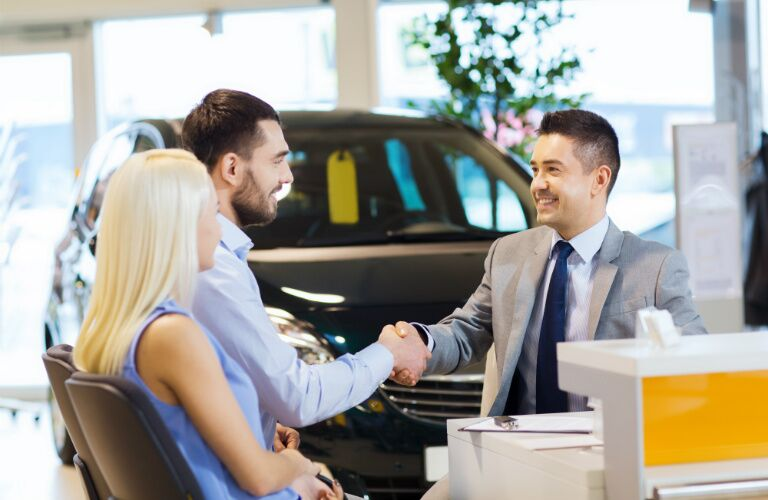 man and woman sitting at desk with salesman in car dealership and shaking hands