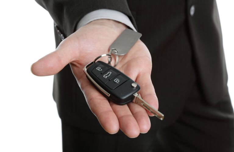 man in suit holding out car key in hand