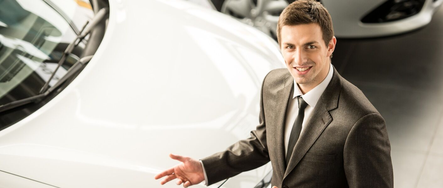 Car salesman standing in front of a car at a dealership