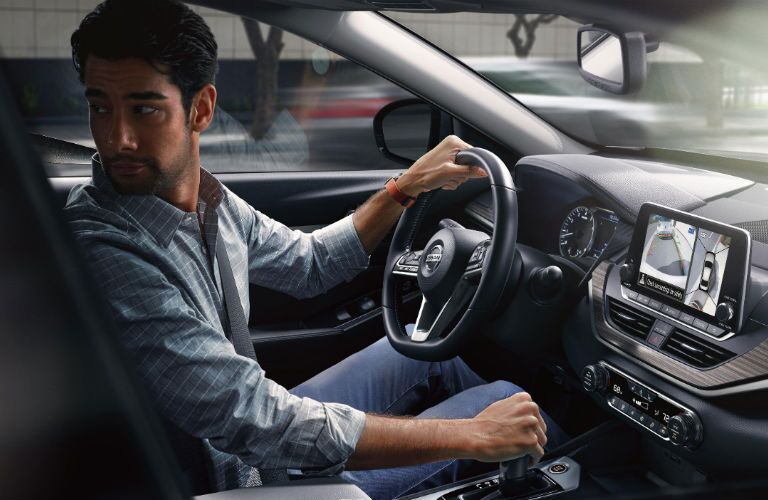 A photo of a person behind the wheel of the 2020 Nissan Altima.