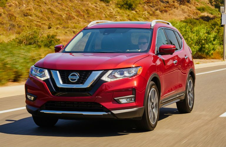A front-end photo of the Nissan Rogue in motion on the road.