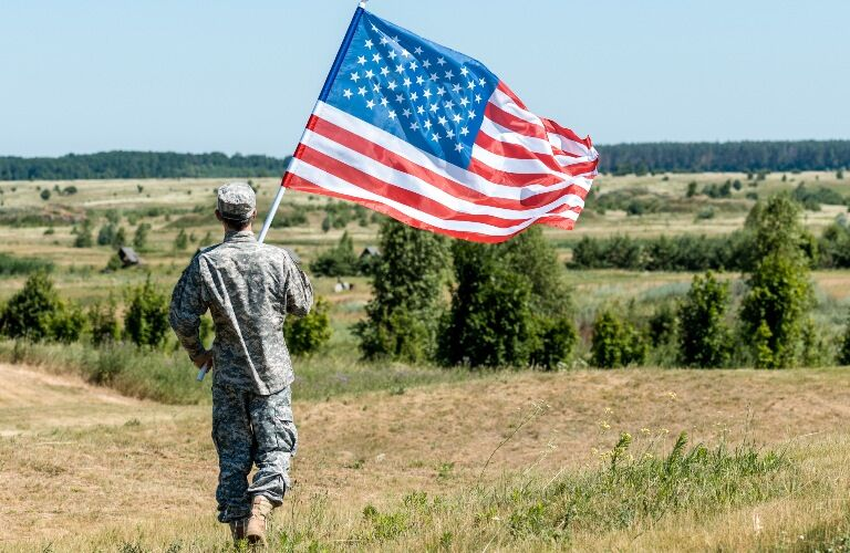 Member of the military carrying the American flag across a field