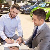 Man signing paperwork as the salesman smiles