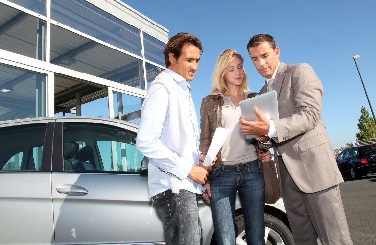 Salesman reviewing information with a young couple outside of the dealership