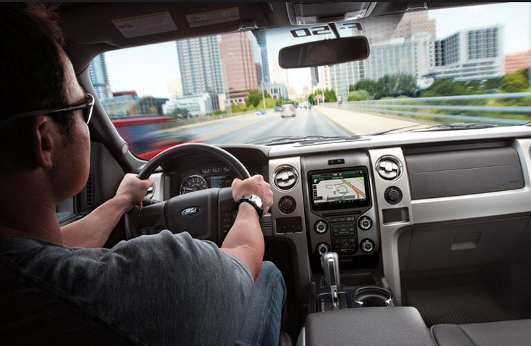 Man driving 2014 Ford F-150 through city