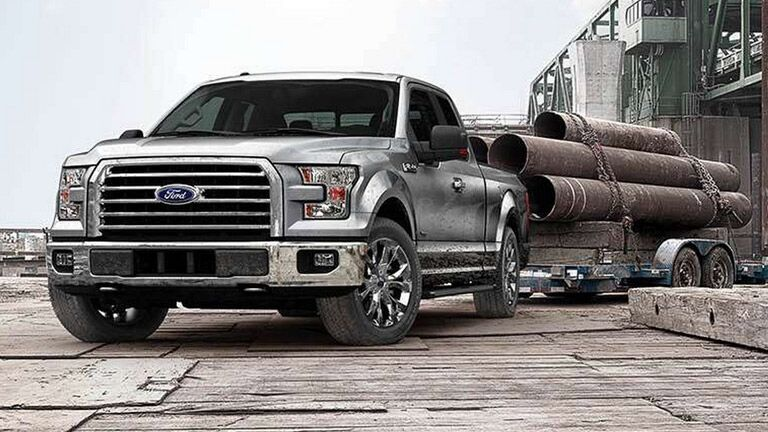Silver Ford F-150 towing trailer on worksite