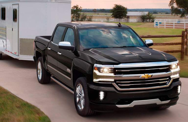 2017 Chevy Silverado in black towing a trailer
