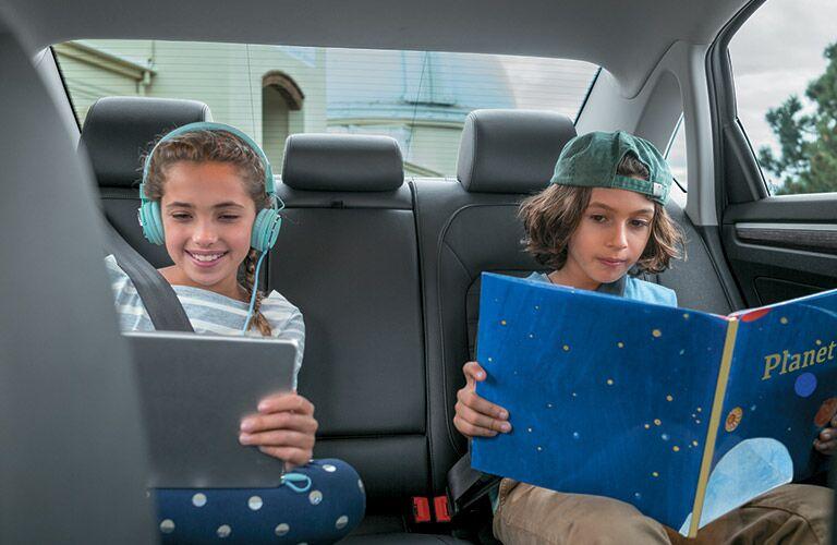2 children in the back of the 2018 Volkswagen Passat reading