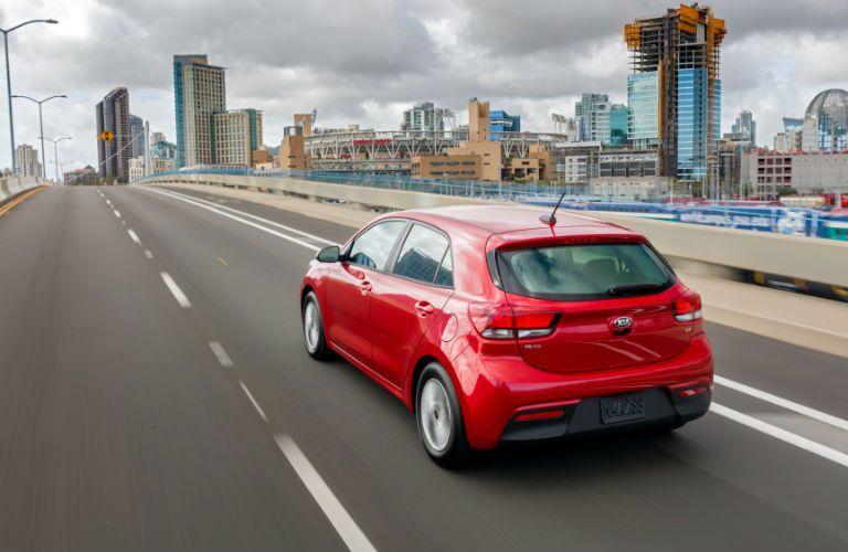 rear view of red 2018 kia rio 5-door driving towards city