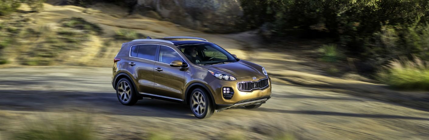 gold 2018 kia sportage driving on gravel road