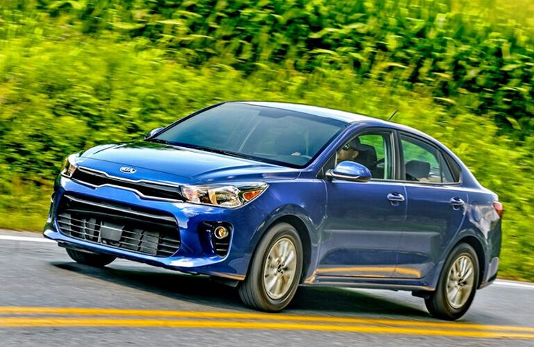 2020 Kia rio blue paint facing left driving on road with plants in background action angle