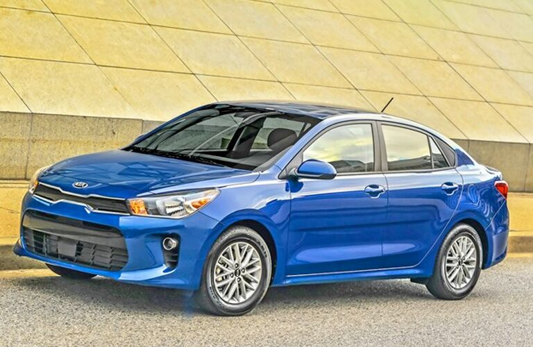 2020 Kia Rio blue paint facing left at an angle with brick background