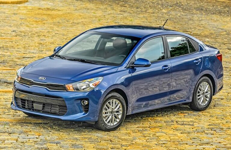 2020 Kia Rio blue paint facing left at an angle with dirt background